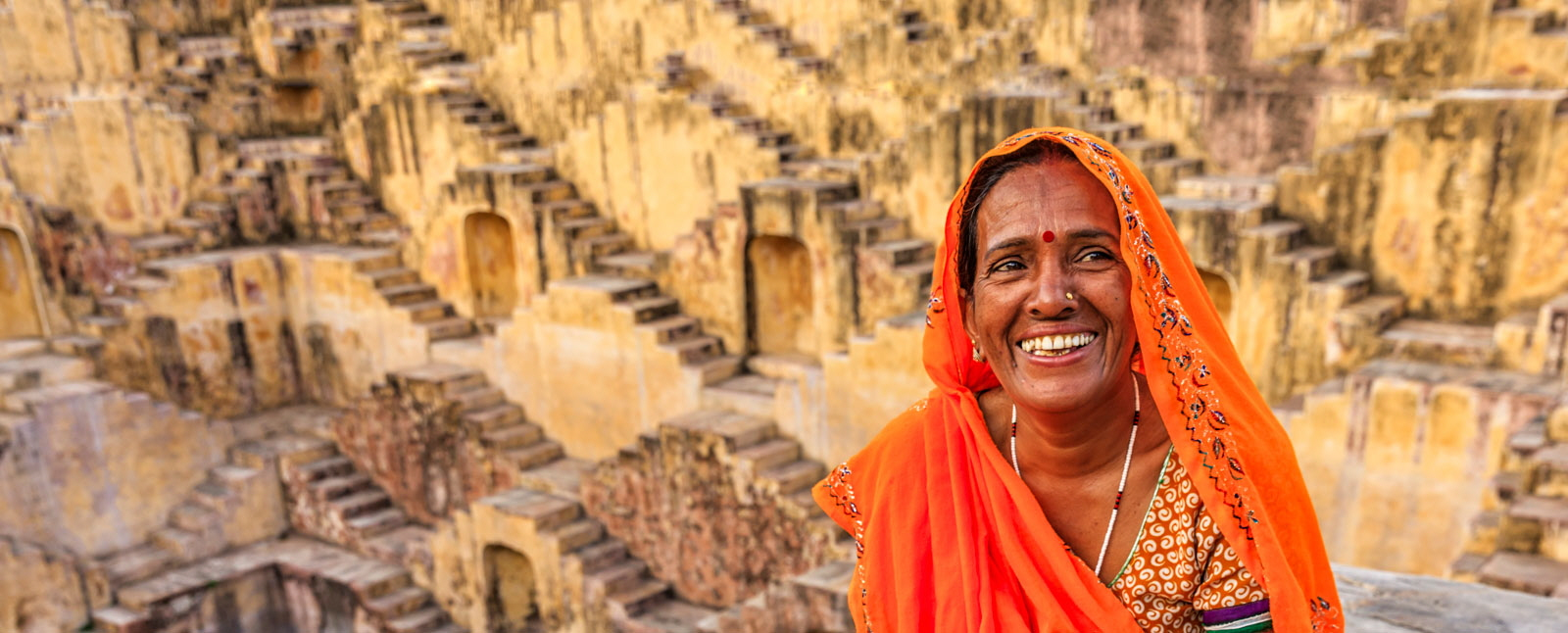 Indian woman resting inside stepwell in village near Jaipur, Rajasthan, India.